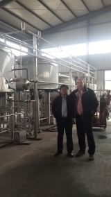 <h5>The Brewery</h5><p>The equipment to make our beer is being made by James and Yucheng Zeyu Machinery Co., LTD. We decided to have our brewery made in China because their quality is good and their cost is very competitive. There are many brewery equipment manufacturers in China and I think these are one of the best. This is James Jia and I standing at the back of the equipment when I inspected the order in Jinan, China, early in 2015. I was very happy with what I saw and very well looked after.</p>